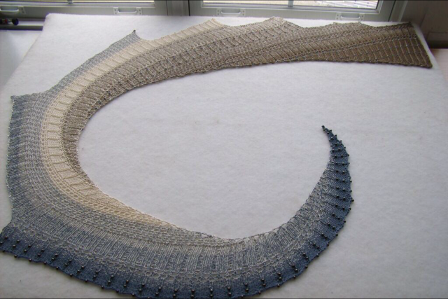 """Lace beaded shawl knitted of long gradient dyed fingering weight cotton. The colour is """"Ebb Tide""""."""